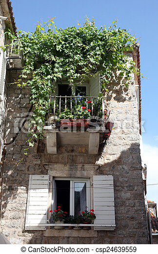 Mediterranean stone medieval house with window shutters and pot plants, Budva, Montenegro