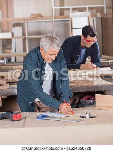 Male Carpenter Working On Blueprint At Workshop