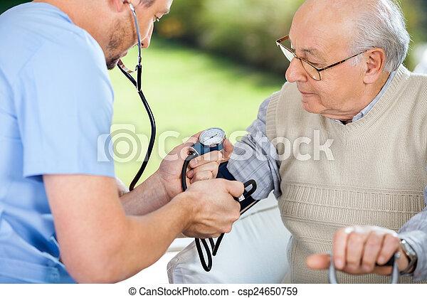 Male Nurse Checking Blood Pressure Of Senior Man