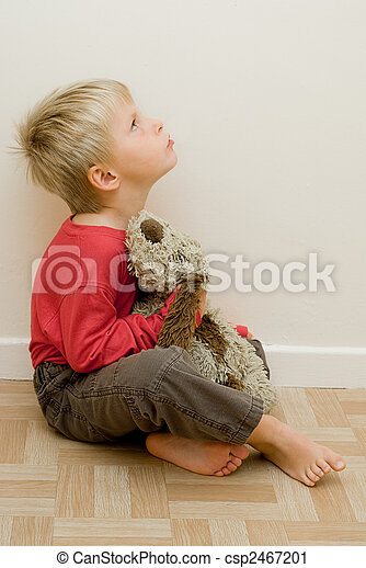 angry child looks upwards holding his toy dog.  - csp2467201