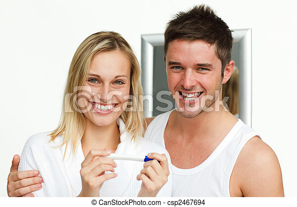 Happy couple examining a pregnancy test smiling at the camera - csp2467694