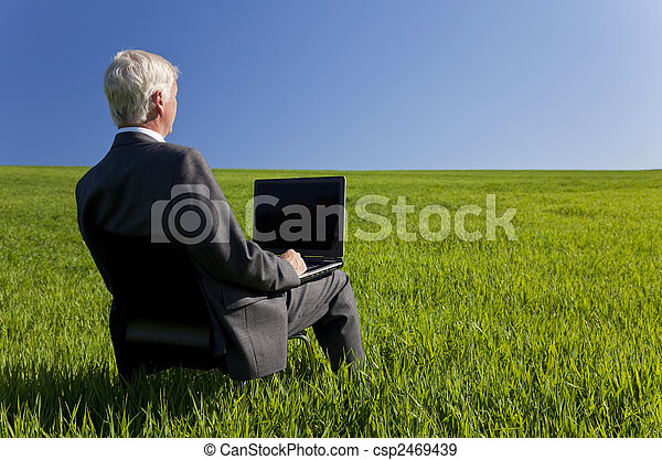 Business concept shot showing an older male executive using a laptop computer in a green field with a blue sky. Shot on location not in a studio. - csp2469439