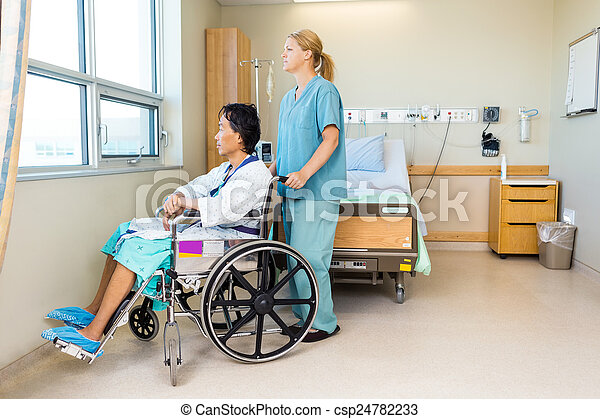 Nurse With Patient Sitting On Wheel Chair At Hospital Window