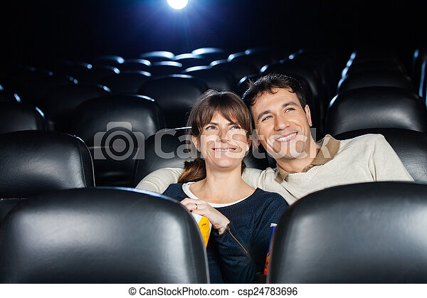 Happy Couple Watching Film In Theater - csp24783696