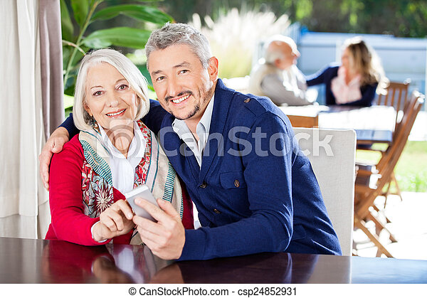 Portrait Of Family Using Smartphone At Nursing Home