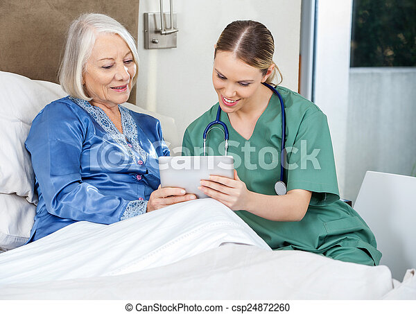 Nurse And Senior Woman Using Tablet PC In Bedroom