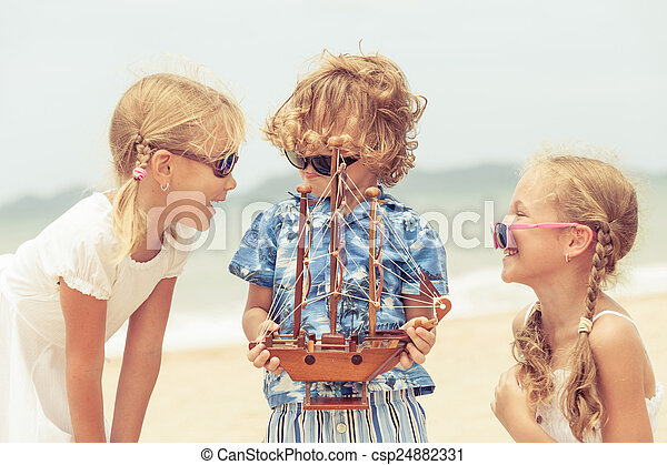 two sisters and brother playing on the beach