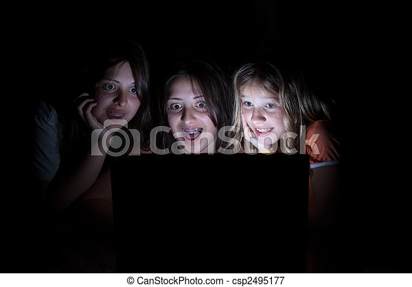 Three young girls sitting in the dark all looking at computer screen with a surprised shocked expression - csp2495177