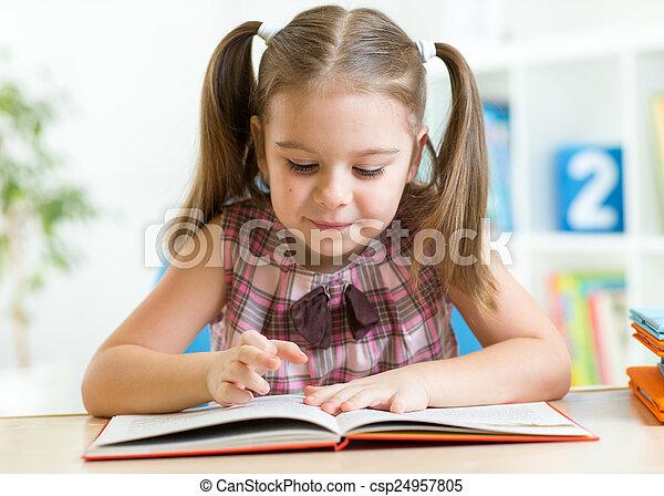 Cute kid girl reading story from big book in nursery