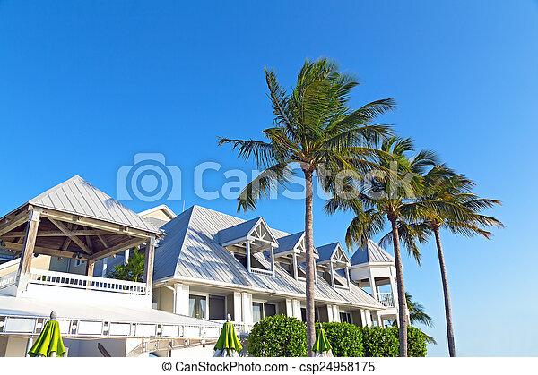 Resort building facing the evening sun. Palms, umbrellas and building before sunset.