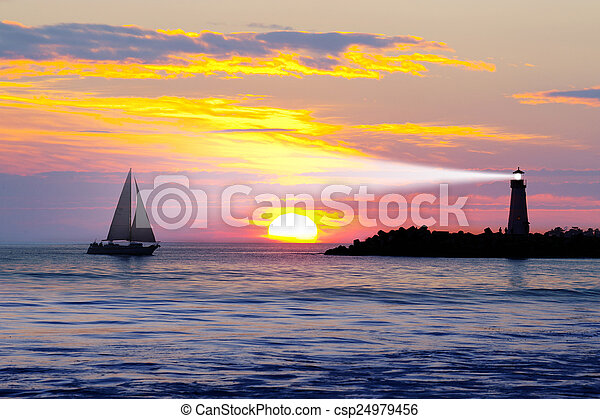 Lighthouse with light beam at sunset - csp24979456