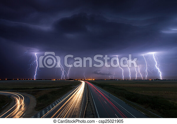 Thunderstorm and lightnings in night over a highway with car lig