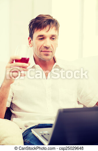 man with laptop computer and glass of rose wine
