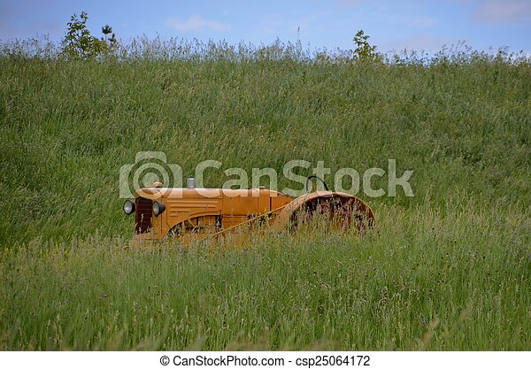 Yellow tractor hidden in grass