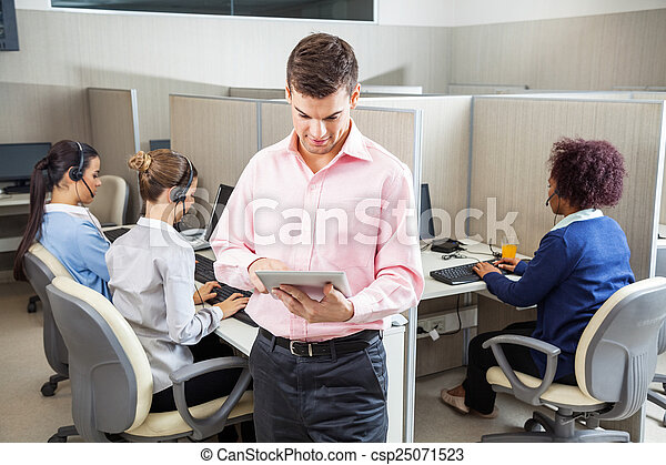 Businessman Using Tablet Computer In Call Center - csp25071523