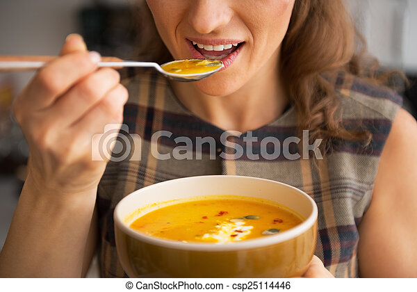 Closeup on young woman eating pumpkin soup in kitchen