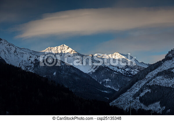 landscape of sun shining on mountain top covered by snow