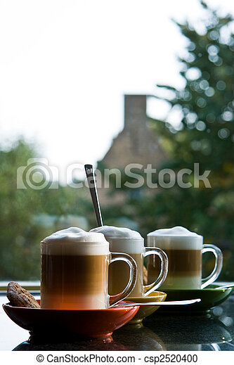 Stock Photography of Three mugs with coffee and cream - vertical