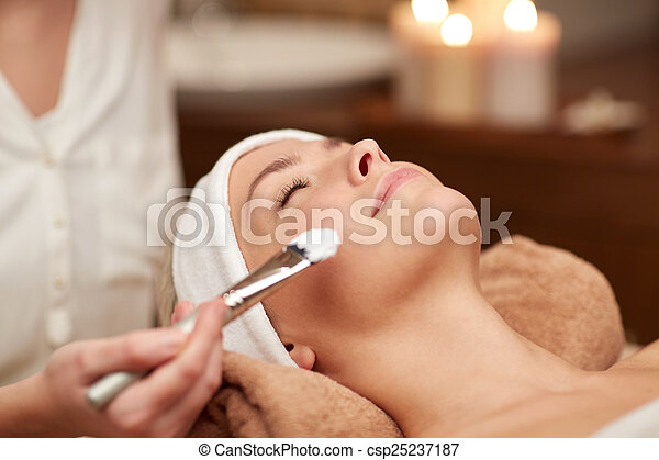 close up of young woman and cosmetologist in spa