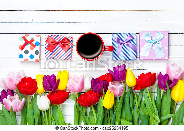 Cup and gift boxes near flowers