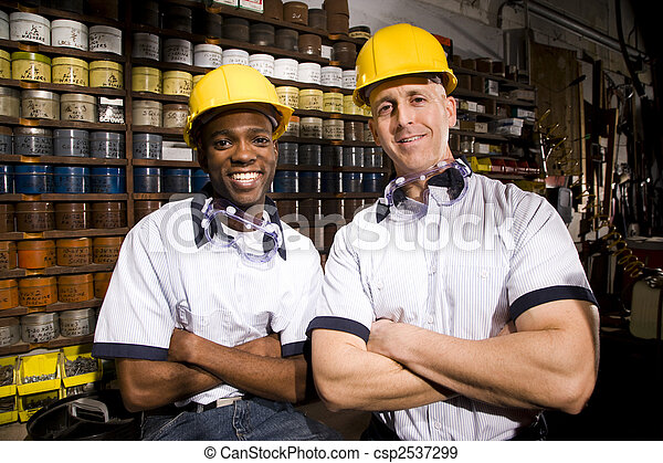 Multi-ethnic male coworkers by shelves of colored inks in print shop - csp2537299