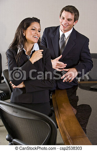 Young Hispanic businesswoman with male colleague in boardroom - csp2538303