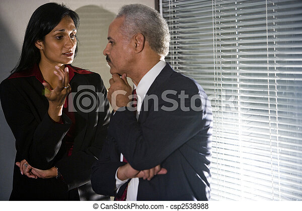 Multi-ethnic businesspeople having discreet conversation in corner of meeting room - csp2538988