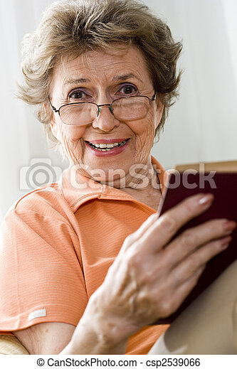 Elderly woman relaxing at home reading a book - csp2539066