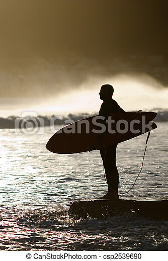 surfer with surfboard looking at waves - csp2539690