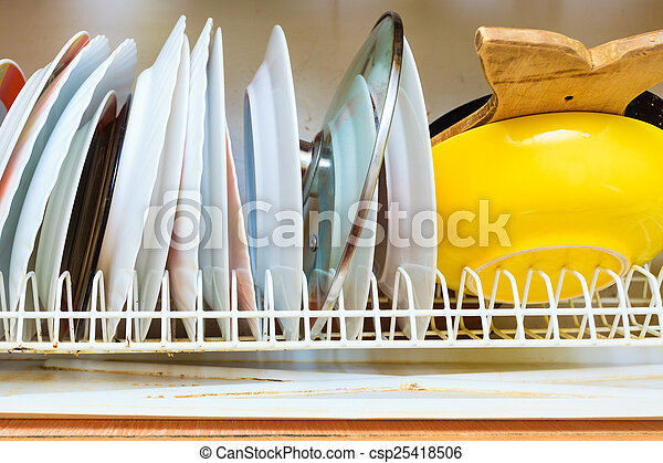 Dirty grubby drainer with clean dishes in kitchen.