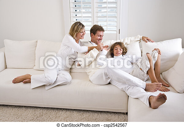 Family relaxing at home on white living room sofa - csp2542567