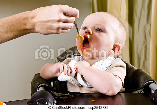 Hungry baby eating solid food from a spoon - csp2542738