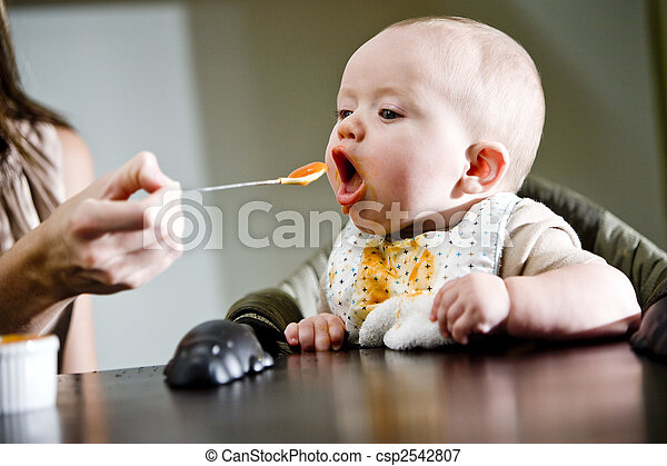 Six month old baby eating solid food - csp2542807