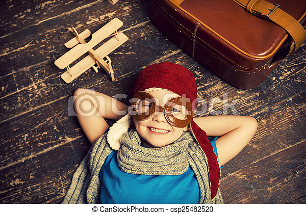 Dreaming of a big sky. Top view of happy little boy in pilot headwear and eyeglasses lying on the hardwood floor and smiling while wooden planer and briefcase laying near him