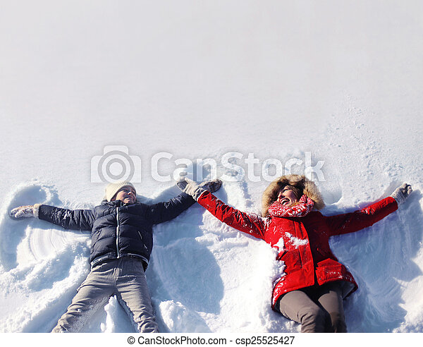 Mother and son having fun together lounging in the snow on a sun