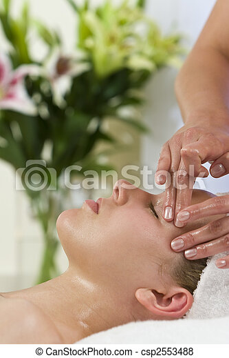 A young woman relaxing at a health spa while having a facial treatment - csp2553488