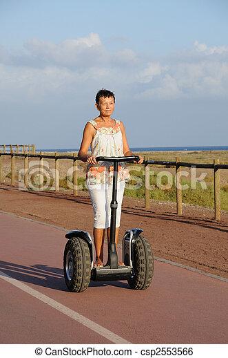 Pensioner woman driving segway - csp2553566