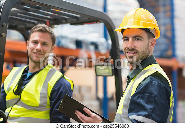 Smiling warehouse worker and forklift driver