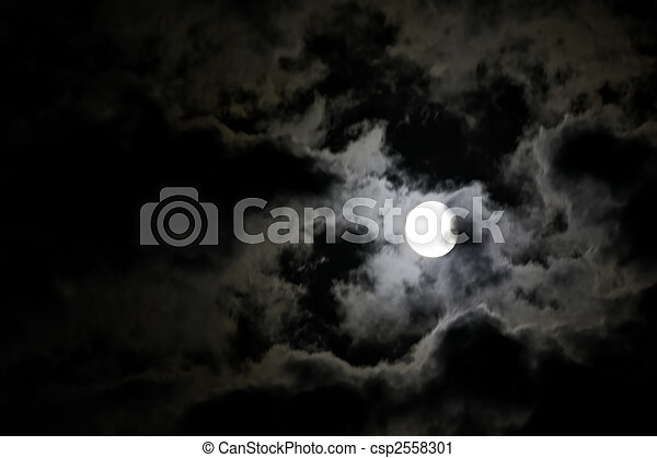 White full moon and eerie white clouds against a black night sky - csp2558301