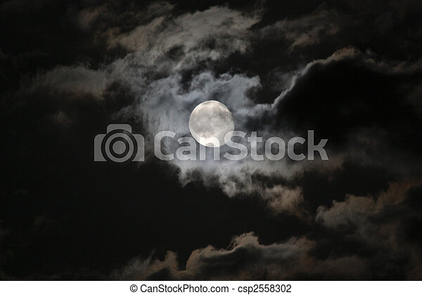 Full moon in eerie white clouds against a black night sky - csp2558302