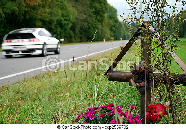 cross with flowers on the edge of a country road for memorial of the many accident victims - csp2559702