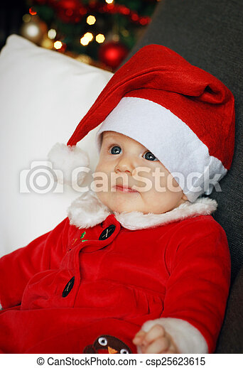 A baby wearing a Christmas costume