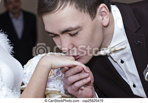 The groom kisses the bride\'s hand