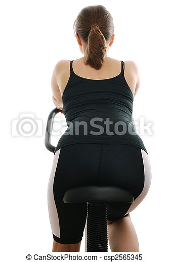 Young woman riding on a spinning bicycle - back - csp2565345