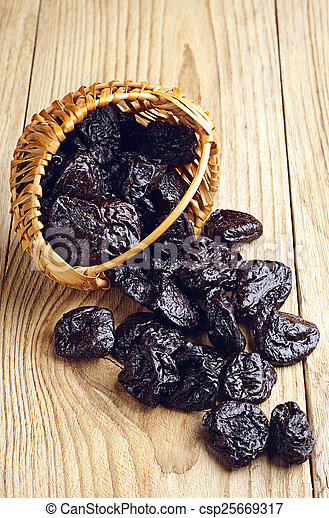 Dried plum in a basket and scattered