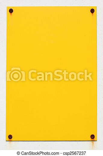 Blank yellow sign stuck to a white wall with rusty screws. - csp2567237