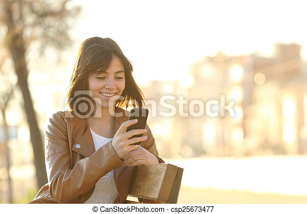 Happy girl using a smart phone in a city park - csp25673477