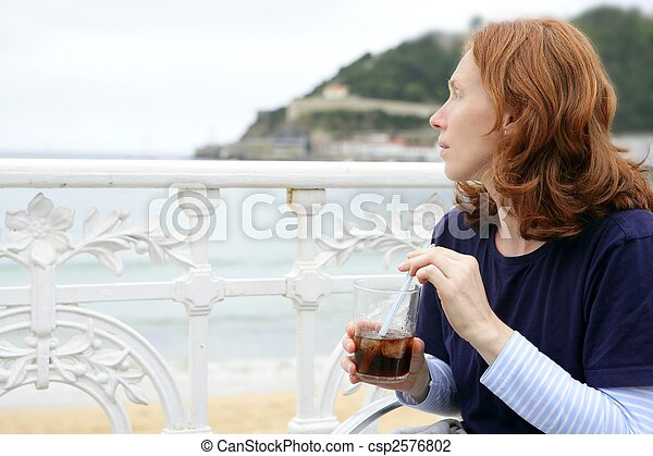 Beautiful redhead woman drinking beverage - csp2576802