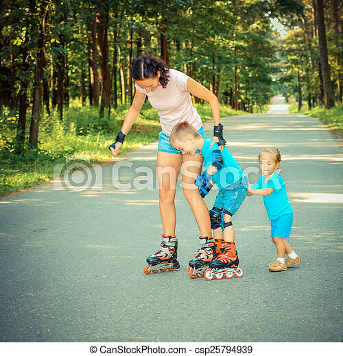 family having fun on roller skates. Mom and kids are engaged in fitness outdoors.