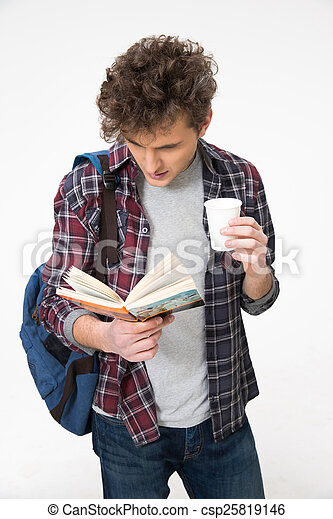 Young male student standing with book and coffee